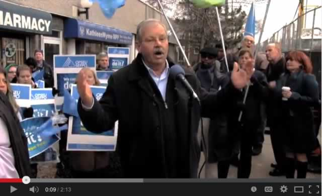 Smokey Thomas speaks at rally while OPSEU members hold up signs around him