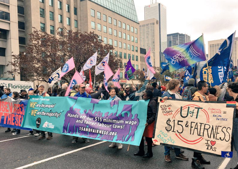 Crowd of people holding up flags and banners, including OPSEU flags, in support of $15 minimum wage and fair labour laws