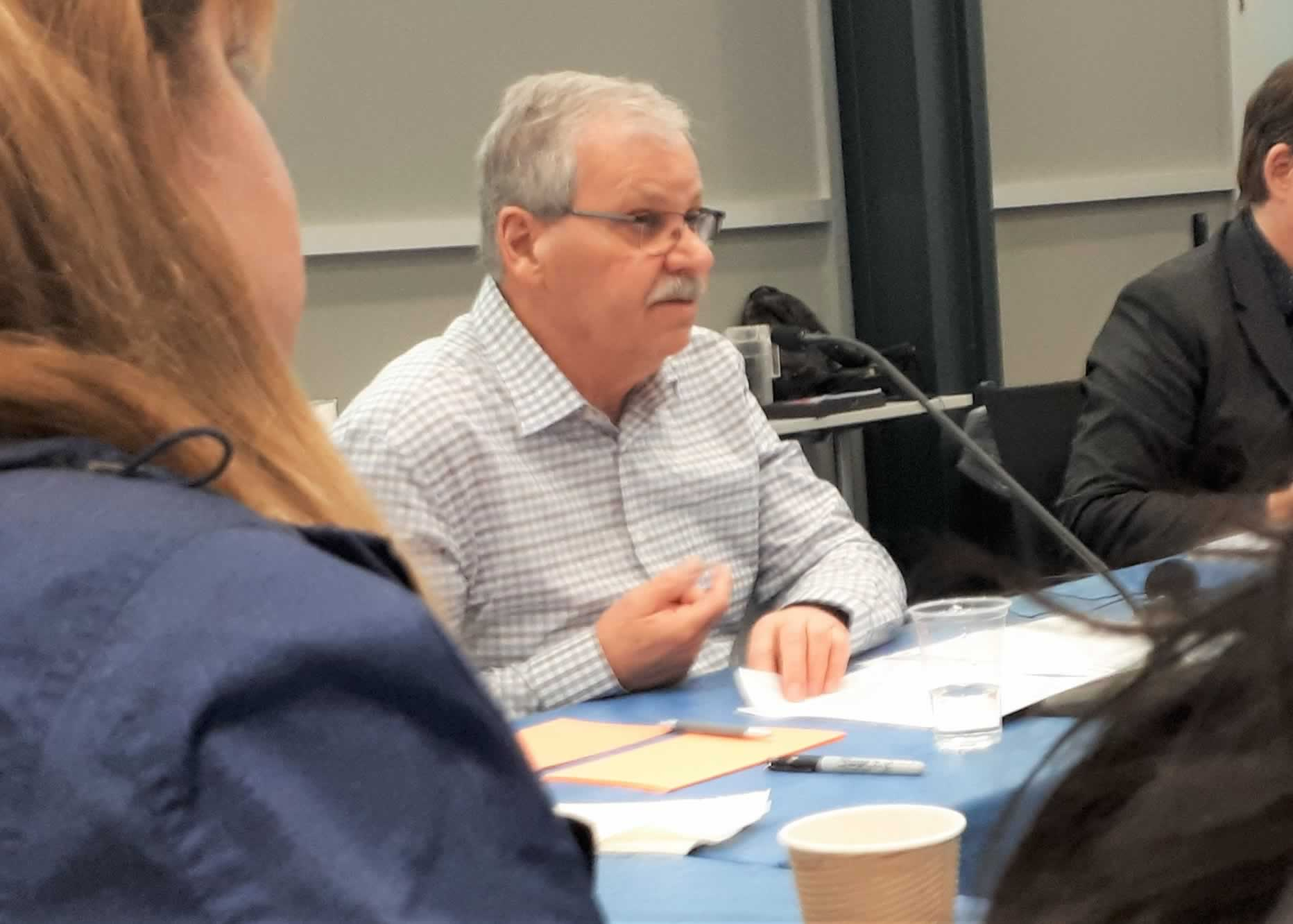 OPSEU President Warren (Smokey) Thomas speaks into a microphone during a telephone town hall.