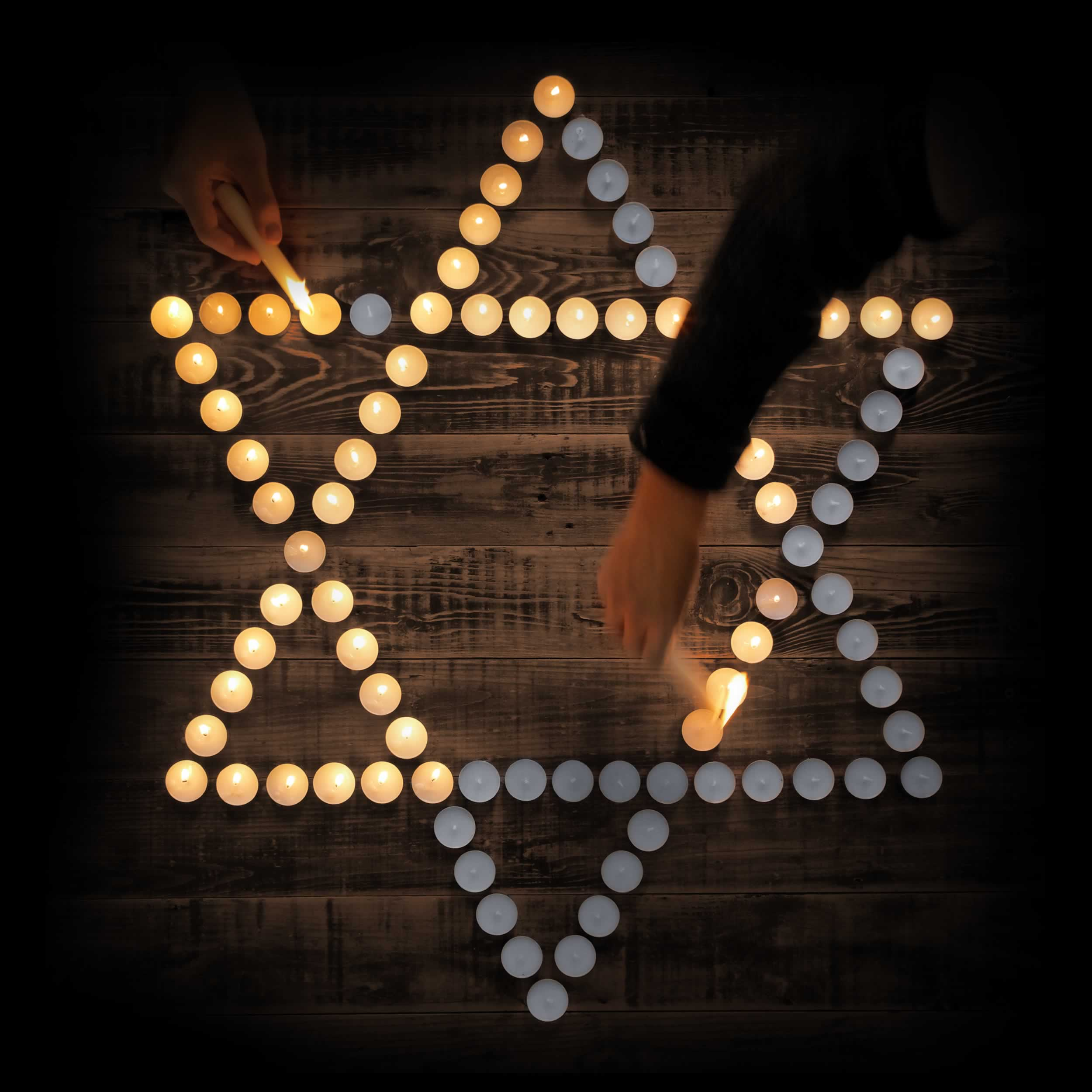 Two people light candles arranged into a Star of David.