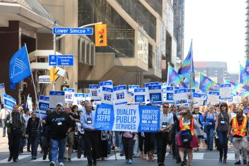 "Large group of OPSEU members holding signs, flags, and a ""Quality Public Services"" banner march in downtown Toronto during Convention 2015"