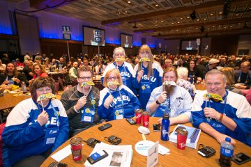 OPSEU members wearing OPSEU hockey shirts and holding campaign moustaches to their faces during Convention 2017 Day 2