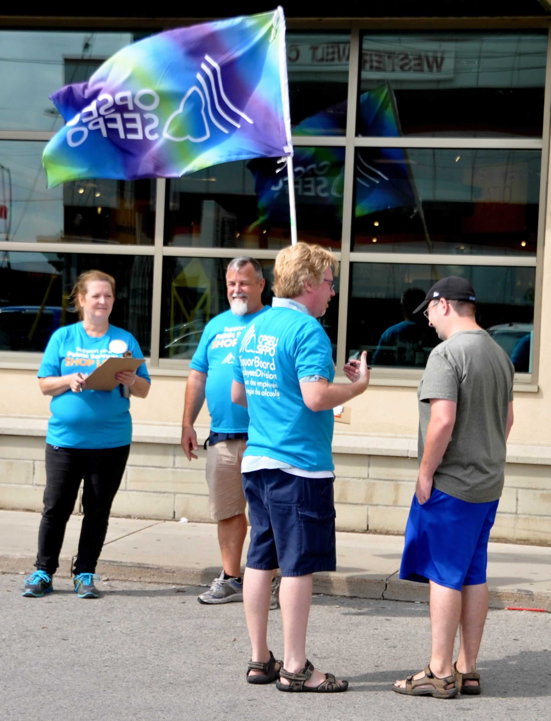 OPSEU members in blue shirts holding flags and clipboards ask a passer-by to sign Shop LCBO cards.signing