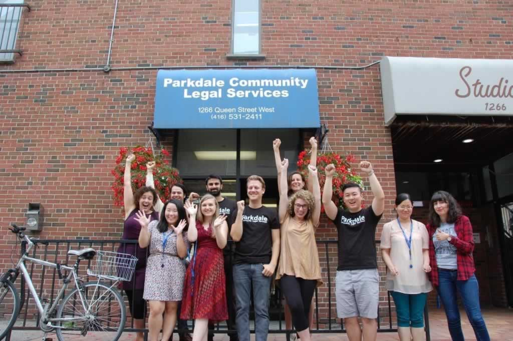 Group of Parkdale Community Legal Services workers with arms raised outside their clinic.