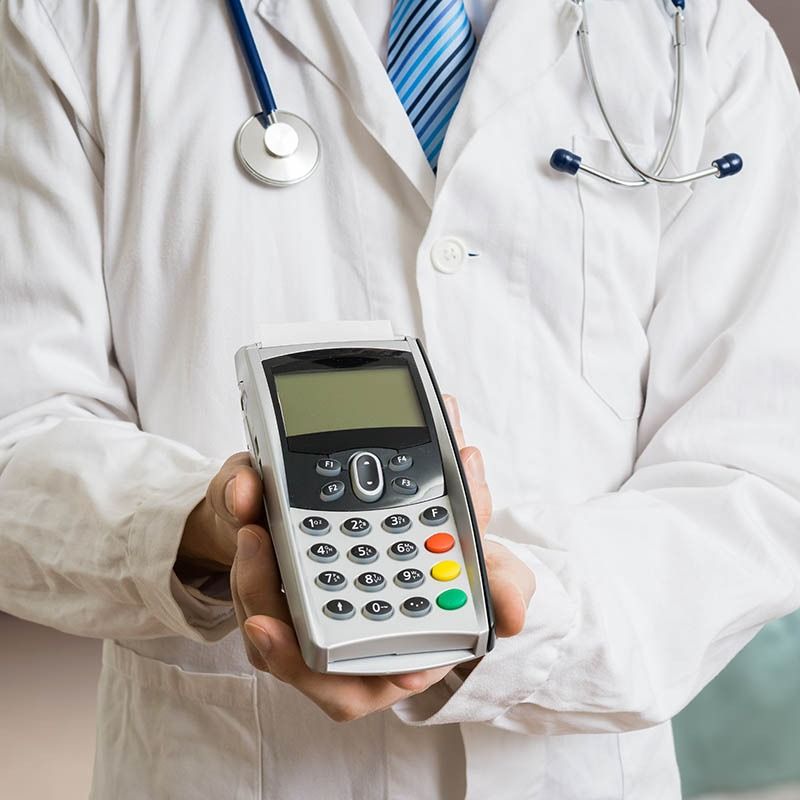 Hospital professional in white coat holding a calculator