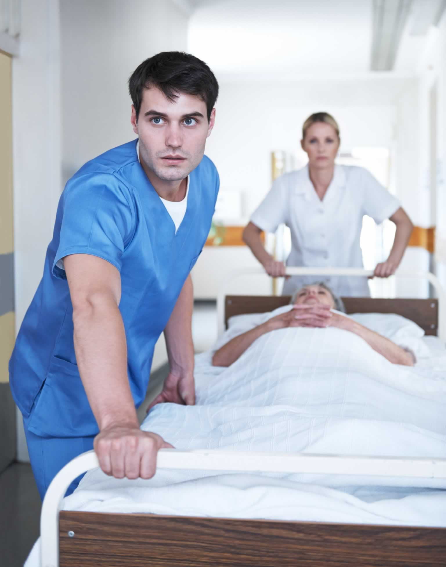 Two health workers in scrubs wheel a patient in a hospital bed.