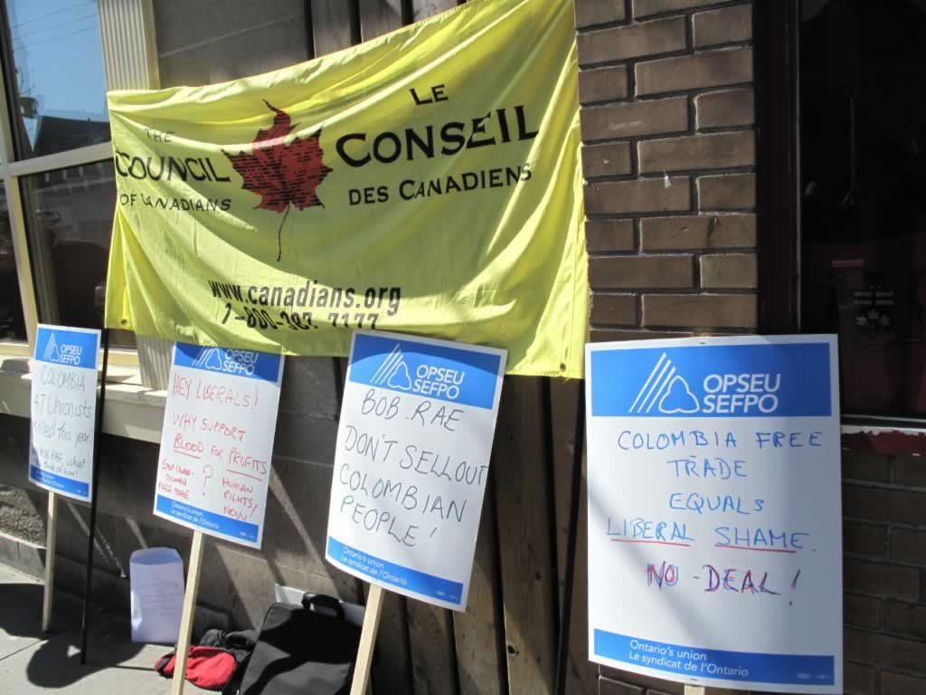 Four OPSEU picket signs with messages about Colombian free trade.