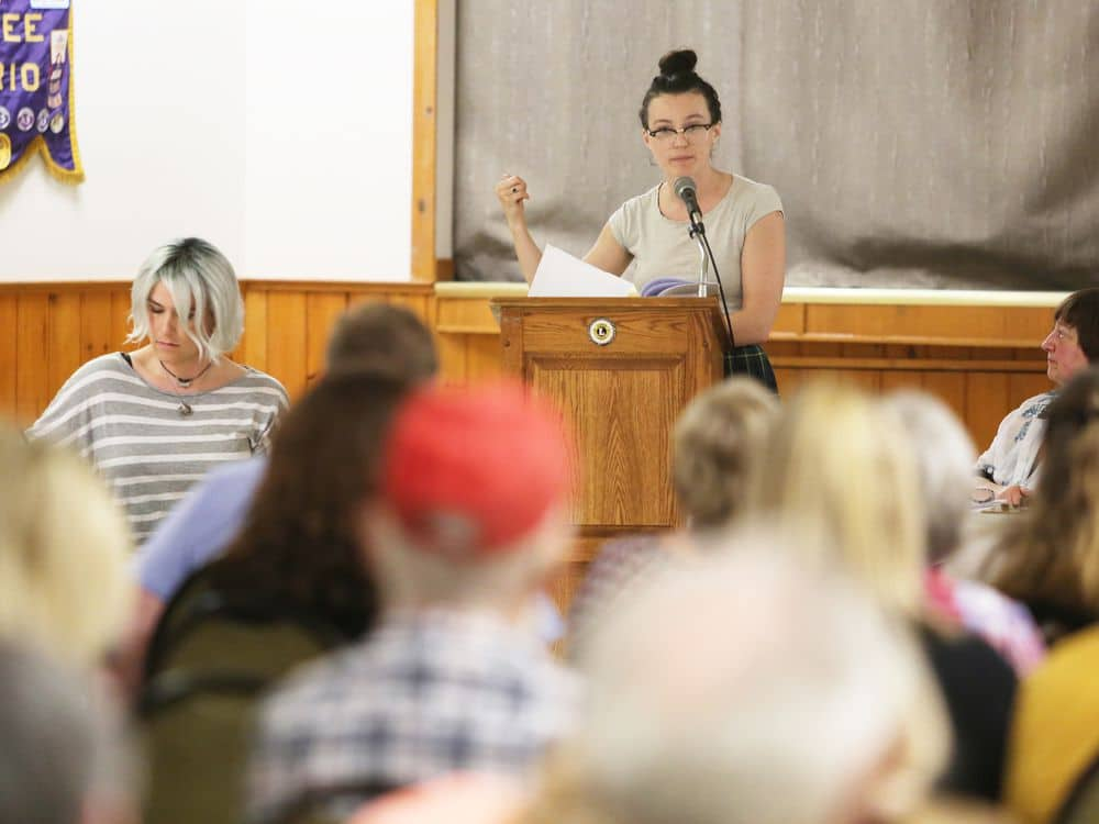 Woman at a podium speaking to a group of people.