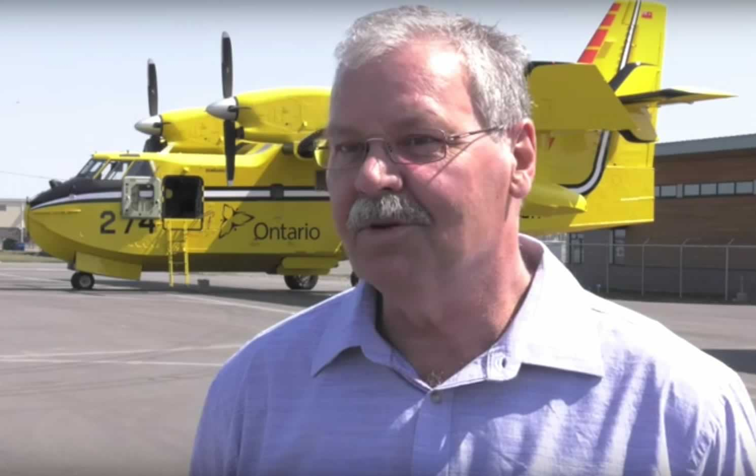 OPSEU President Warren (Smokey) Thomas in front of a MNRF firefighting airplane.
