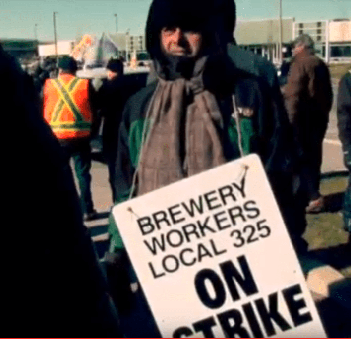 """Striker at Molson Coors holding a picket sign that says """"Brewery Workers Local 325 On Strike"""""""