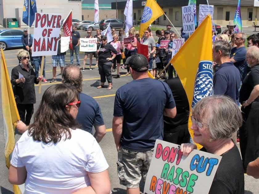 Large group of workers holding picket signs and flags, including OPSEU flags, during rally.