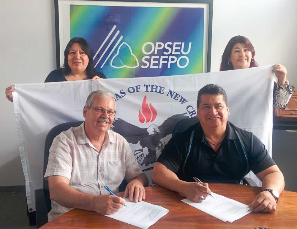 OPSEU President Warren (Smokey) Thomas and Mississaugas of the New Credit First Nation Chief R. Stacey Laforme sign the MOU while members of the Indigenous Mobilizing Team watch.