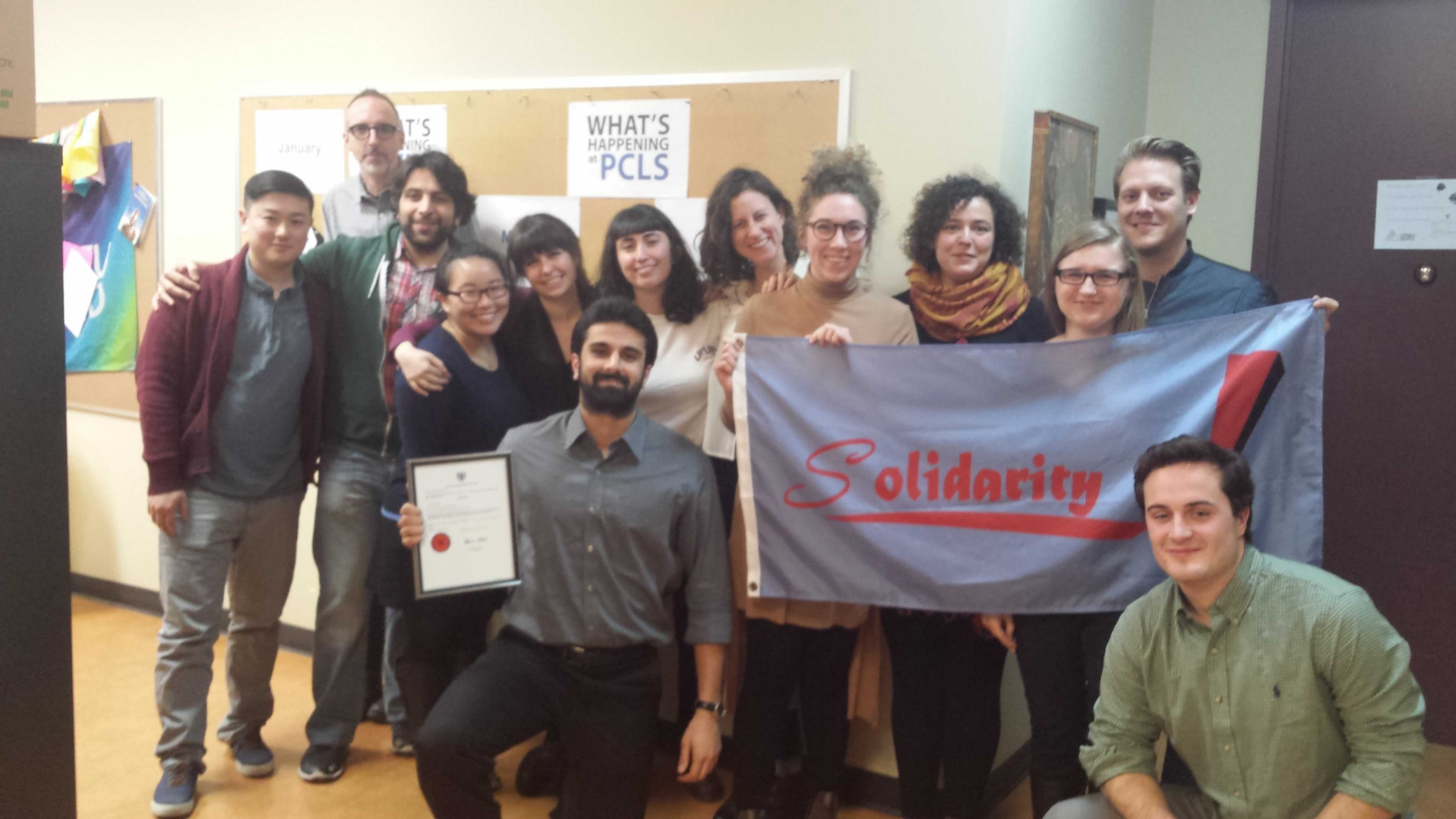 """Summer caseworkers at Parkdale Community Legal Services hold a """"Solidarity!"""" banner"""