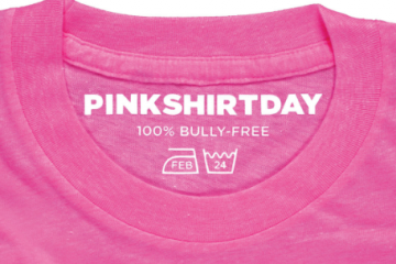 "Pink shirt with ""Pink Shirt Day, 100% Bully-Free"" written on the tag."