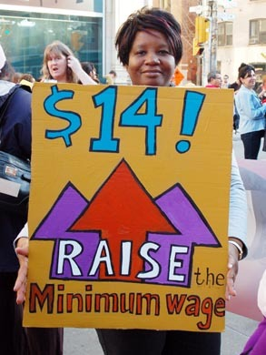 """Woman holds a sign that says """"$14! Raise the minimum wage."""""""