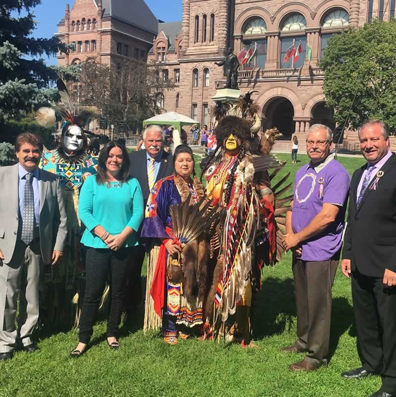 Warren (Smokey) Thomas standing with group in front of Queens Park during Pow Wow