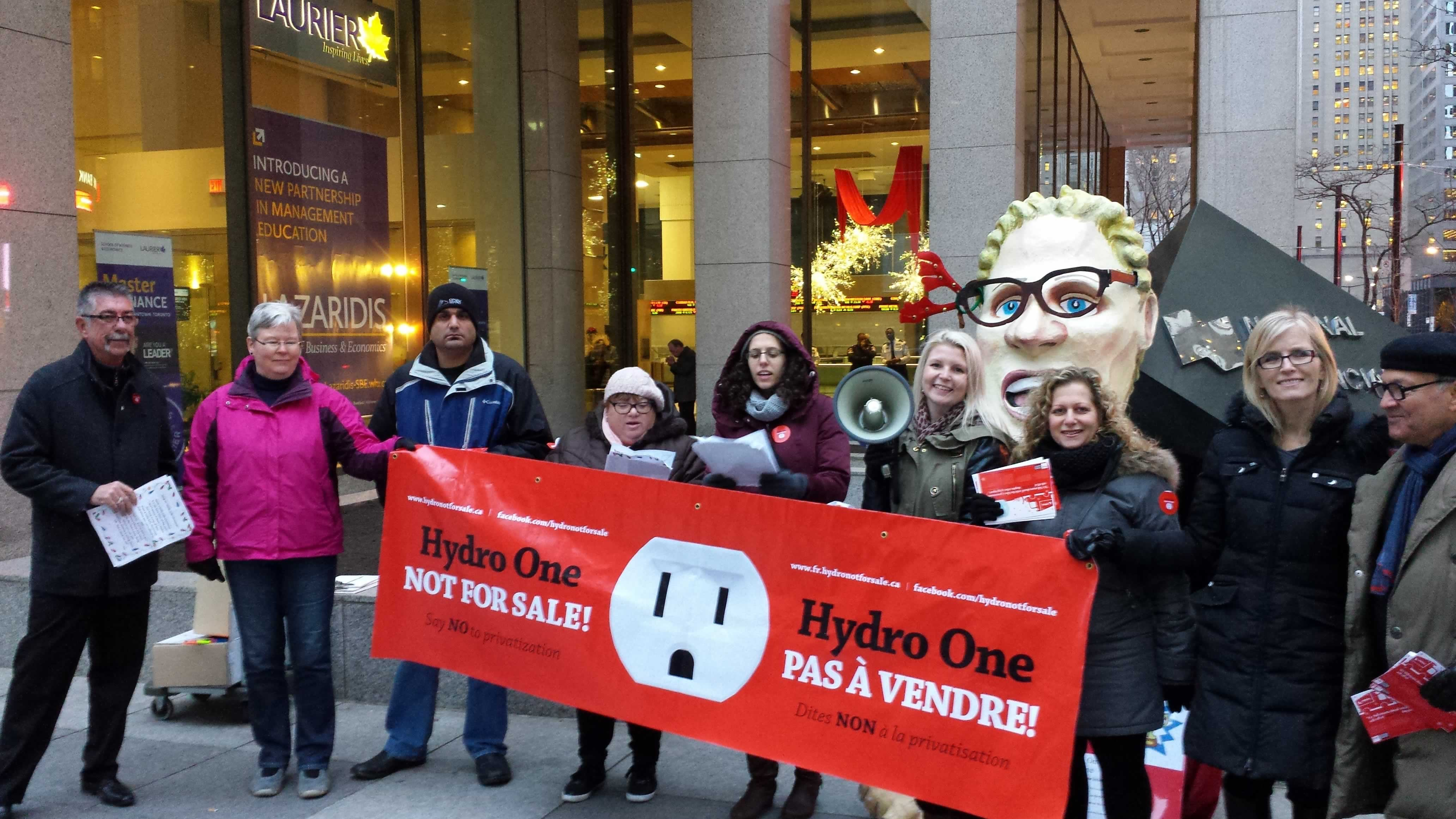 "OPSEU and OFL members hold a ""Hydro One Not for Sale"" banner during a rally."