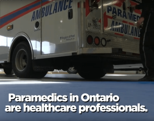 "Ambulance in garage with the caption ""Paramedics in Ontario are healthcare professionals."""