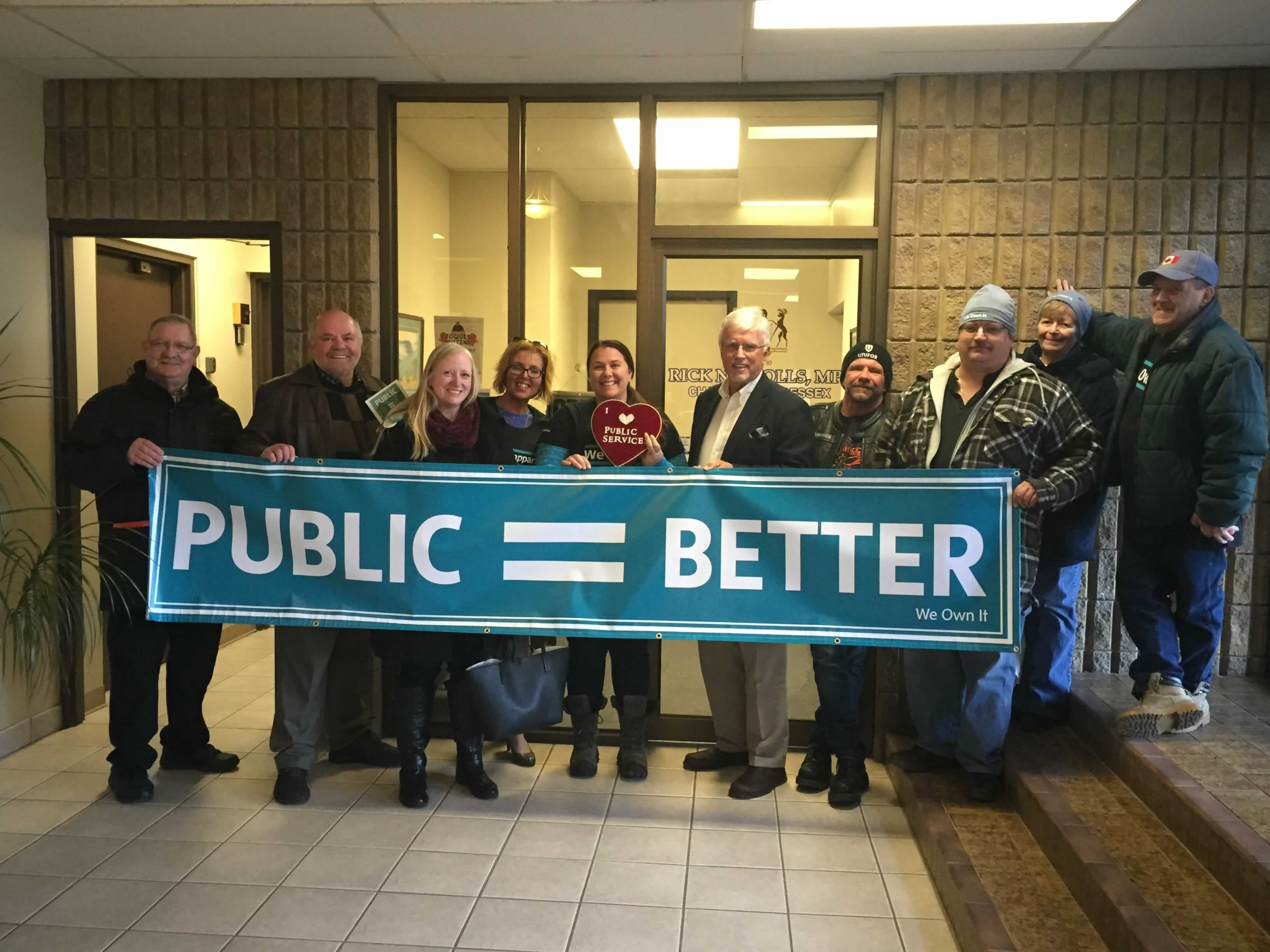 """We Own it campaign supporters hold a """"Public = Better"""" banner with Conservative MPP Rick Nicholls"""