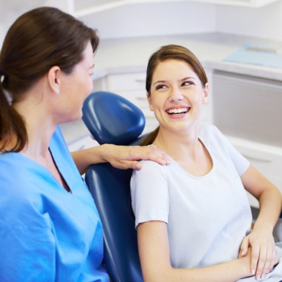 Woman in dentist's chair smiling at a dentist.