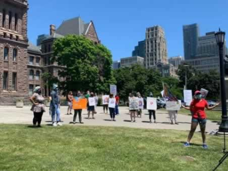 Members holding signs outside Queen's Park