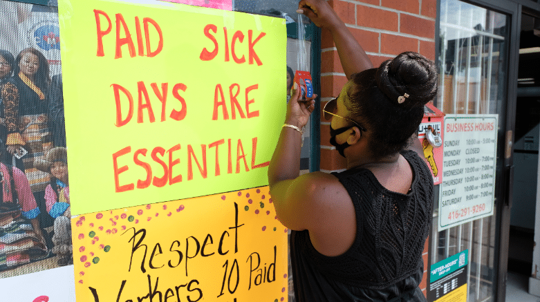 Woman puts up sign saying Paid Sick Days are Essential
