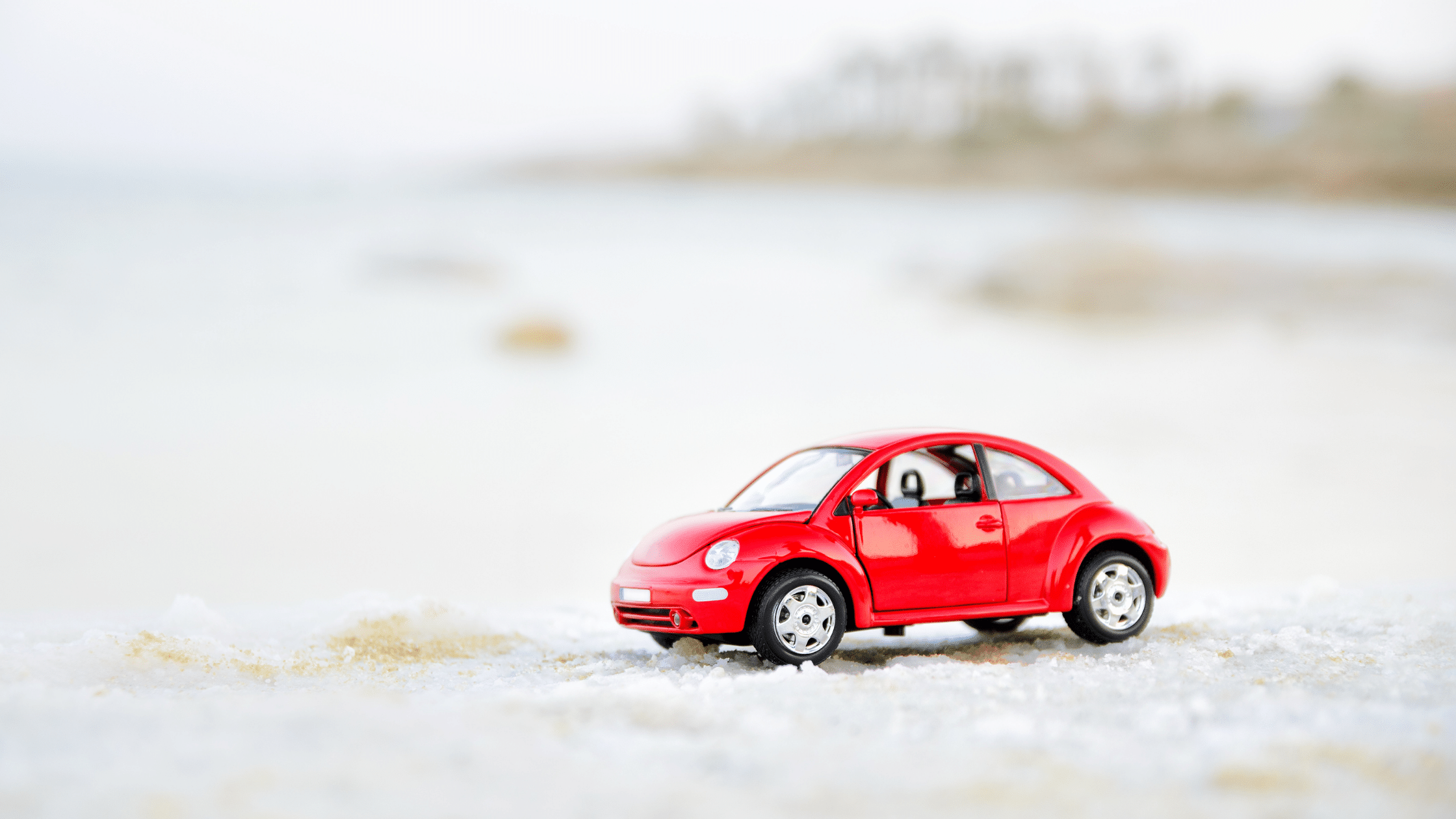 Red toy car driving in the snow