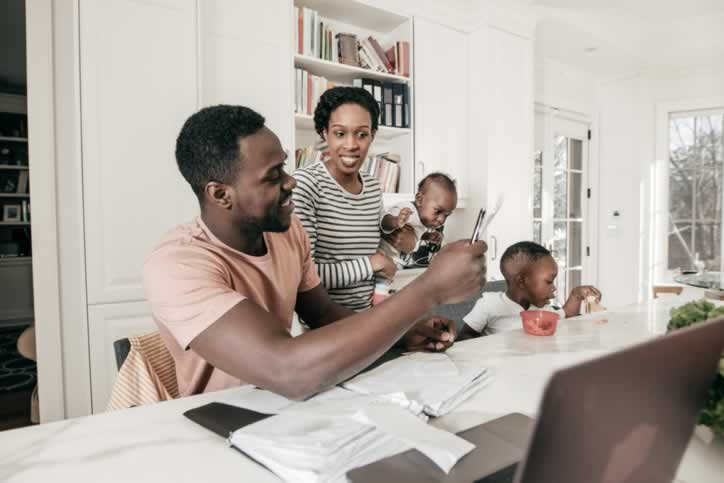 Parents look at a cellphone and paper while caring for two children.