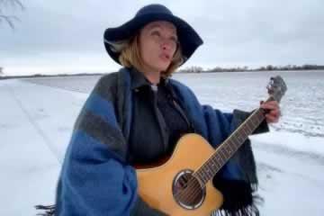 OPSEU/SEFPO Local 154 member Janice Hunter playing guitar and signing
