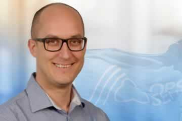 Julius Arscott smiling in front of OPSEU/SEFPO Flag