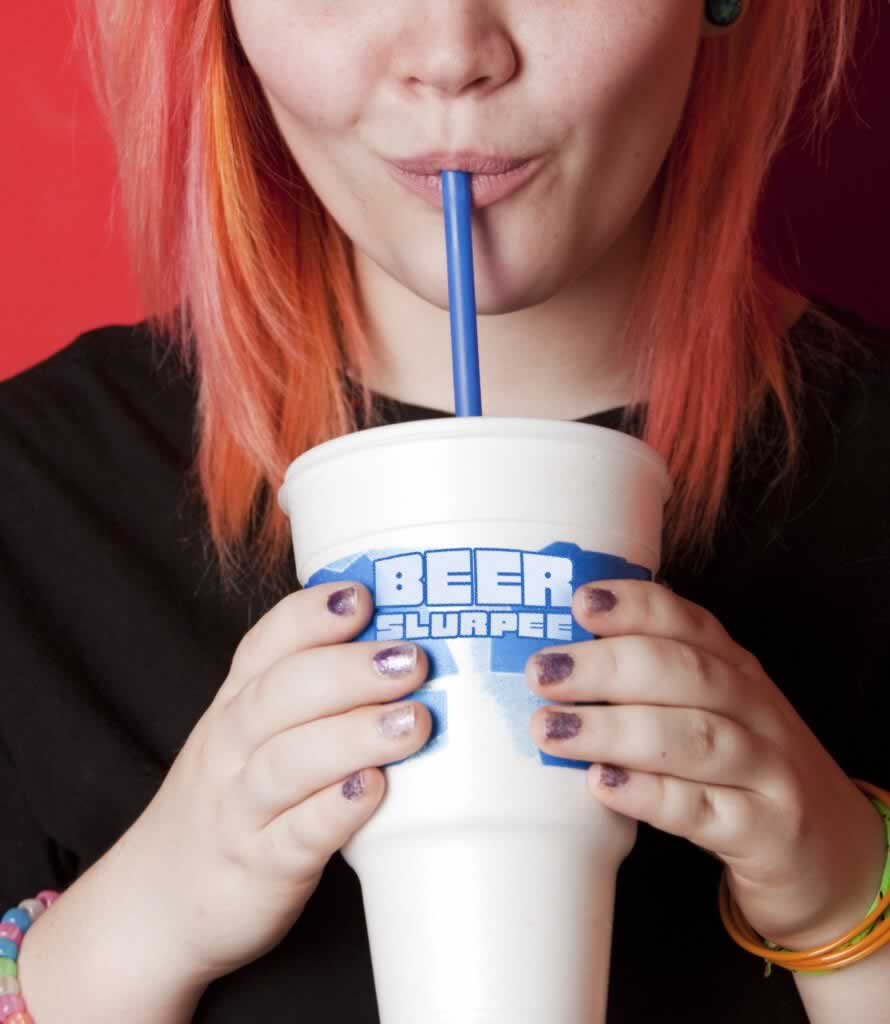 Girl taking a drink out of a beer slurpie glass