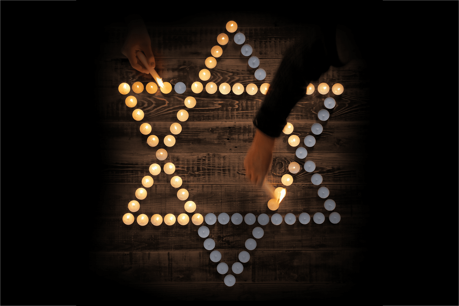 Two people lighting candles in the shape of the Jewish Star of David.