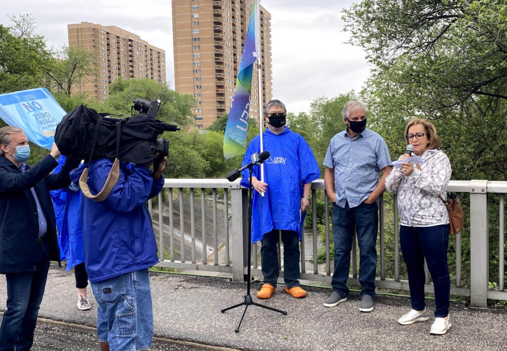 Journalists film and take pictures as OPSEU/SEFPO President Warren (Smokey) Thomas, Local 5117 President and Bargaining Team Chair, Mahnaz Pourahmadi, and OPSEU/SEFPO Executive Board Member Kingsley Kwok speak.