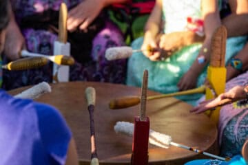 Close-up of the hands of people participating in a drumming circle.